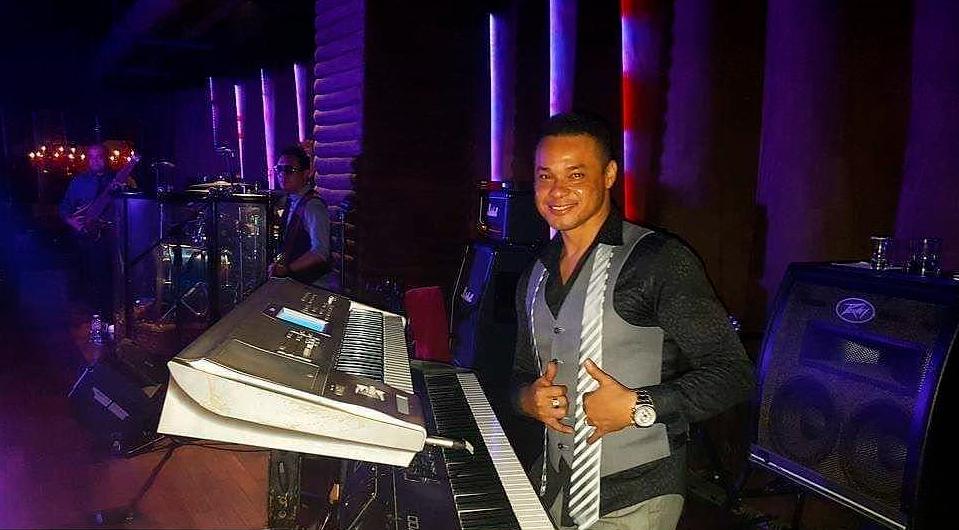 Alex Pérez toca el piano en una presentación con luces moradas y viste de traje negro con gris.