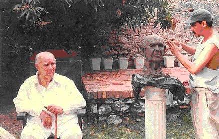 El escritor cartagenero Donaldo Bossa Herazo está sentado en el patio del Palacio de la Inquisición de Cartagena de Indias, Colombia. Posa mientras el escultor Alfredo Tatis Benzo le hace un busto.