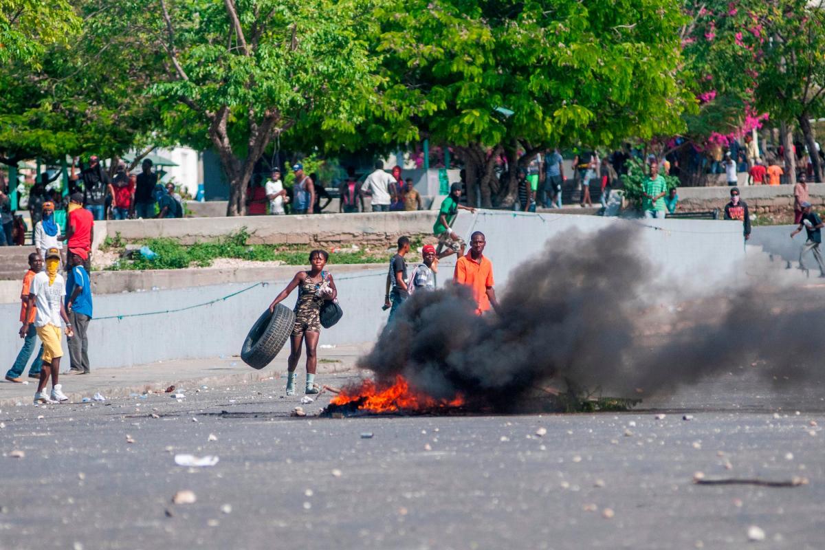 Personas participan en una protesta en Puerto Príncipe (Haití). La crisis política que vive Haití se agrava al cumplirse este jueves una semana de violentas protestas en reclamo de la renuncia del presidente Jovenel Moise, las cuales han dejado al menos nueve muertos. EFE/ Jean Marc Herve Abelard