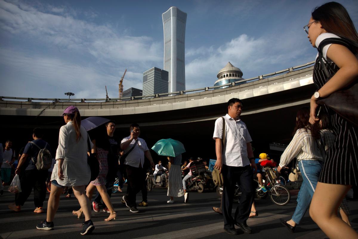 """La gente cruza la calle en un sendero de peatones en el distrito central de negocios de Pekín, este viernes en el que aumenta la ofensiva de propaganda contra Washington. Los medios estatales de China acusaron a EE. UU. de buscar """"colonizar negocios globales"""" apuntando a equipos de telecomunicaciones Huawei gigante y otras empresas chinas. Foto AP / Mark Schiefelbein"""