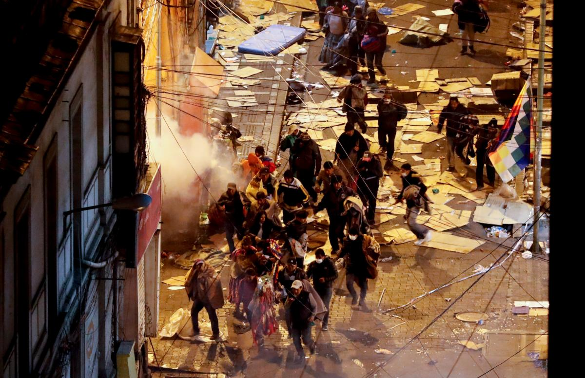 Los partidarios del ex presidente Evo Morales escapan de las nubes de gases lacrimógenos arrojados por la policía en La Paz, Bolivia. AP Natacha Pisarenko