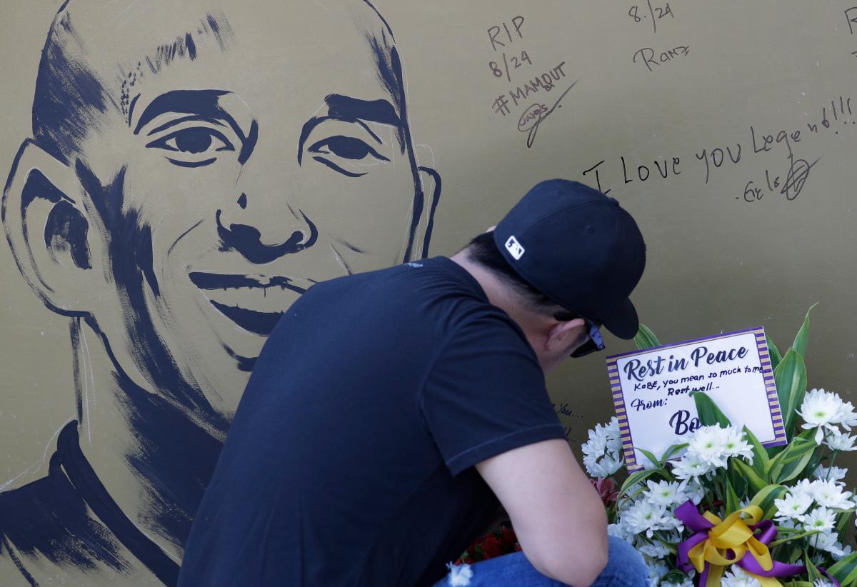 """Un fanático escribe un mensaje en una pared con una imagen del ex jugador de baloncesto de la NBA Kobe Bryant en la cancha de baloncesto """"House of Kobe"""" en Valenzuela, al norte de Manila, Filipinas. AP Aaron Favila"""