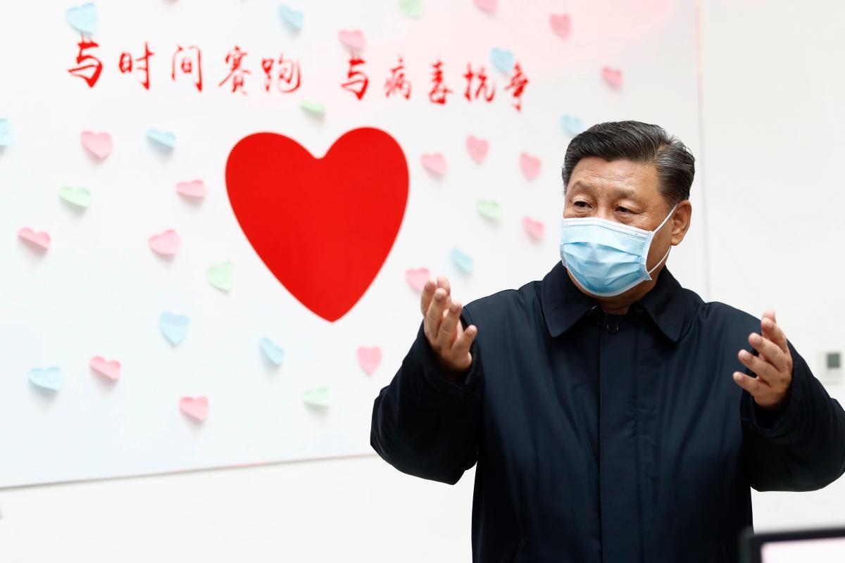 """El presidente chino Xi Jinping hace un gesto cerca de un letrero en forma de corazón y el lema """"Carrera contra el tiempo, lucha contra el virus"""" durante una inspección del centro para el control y prevención de enfermedades de Chaoyang Distrito de Beijing. AP Liu Bin"""