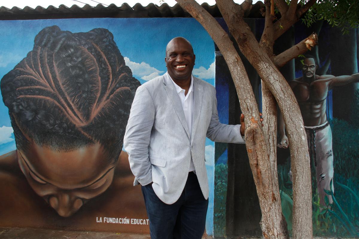 James Guitard con uno de los murales del Barrio Chino de fondo.