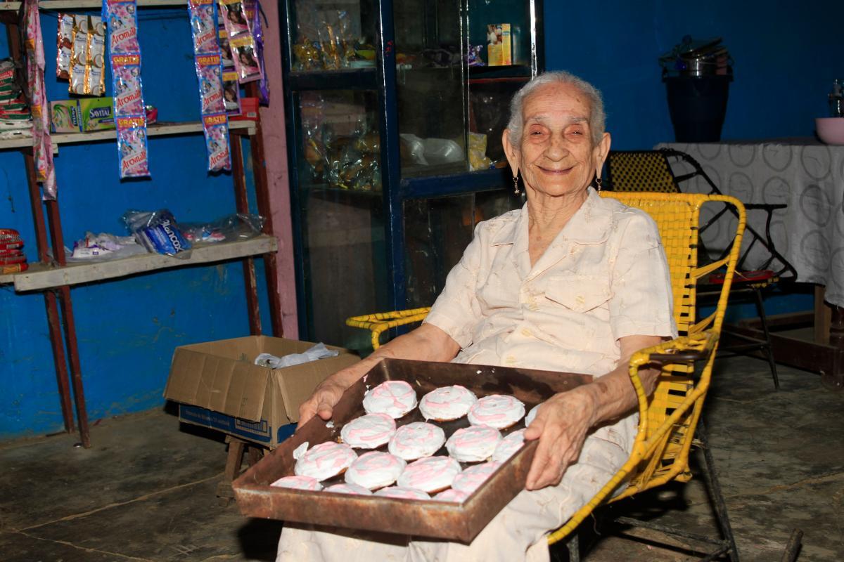 La bolivarense María Narciza Bustillo posa para una fotografía mientras está sentada y sostiene una bandeja con galletas en su casa en San Juan Nepomuceno, Bolívar.