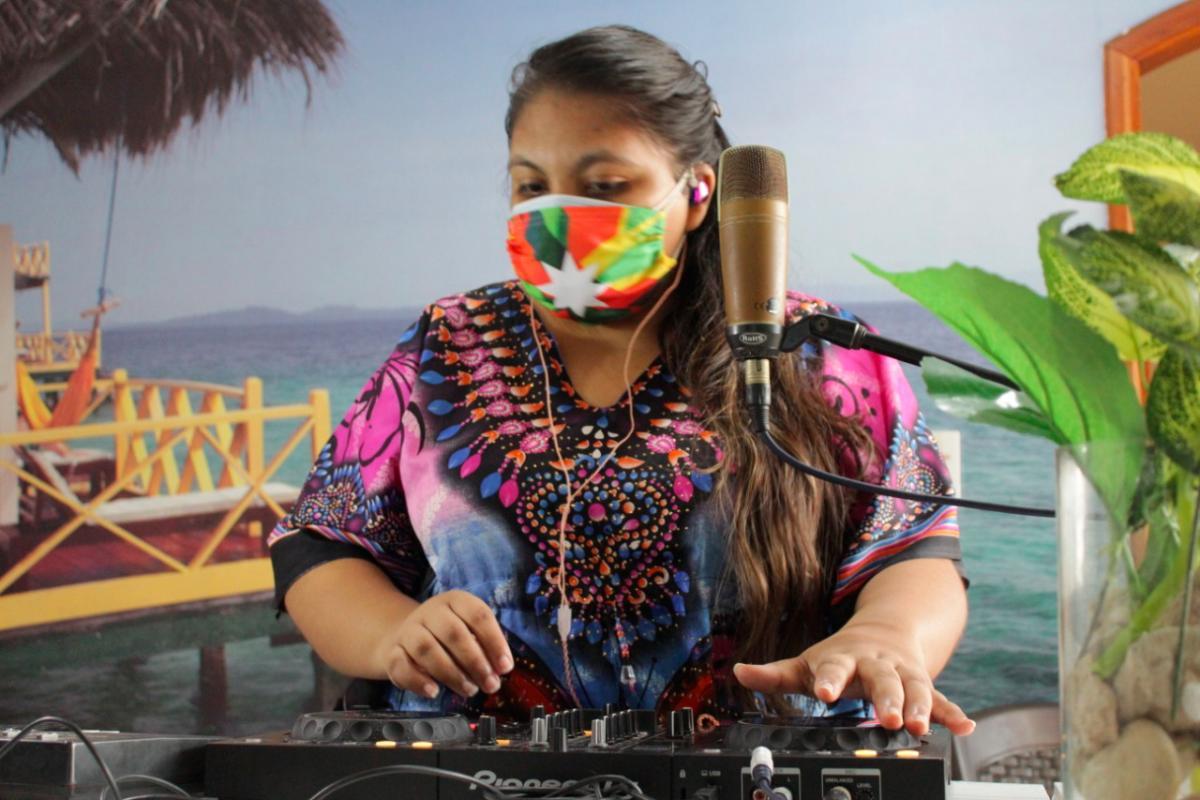 La artista turbanera Mily Iriarte toca su controladora. Usa un tapabocas con la bandera de Cartagena.