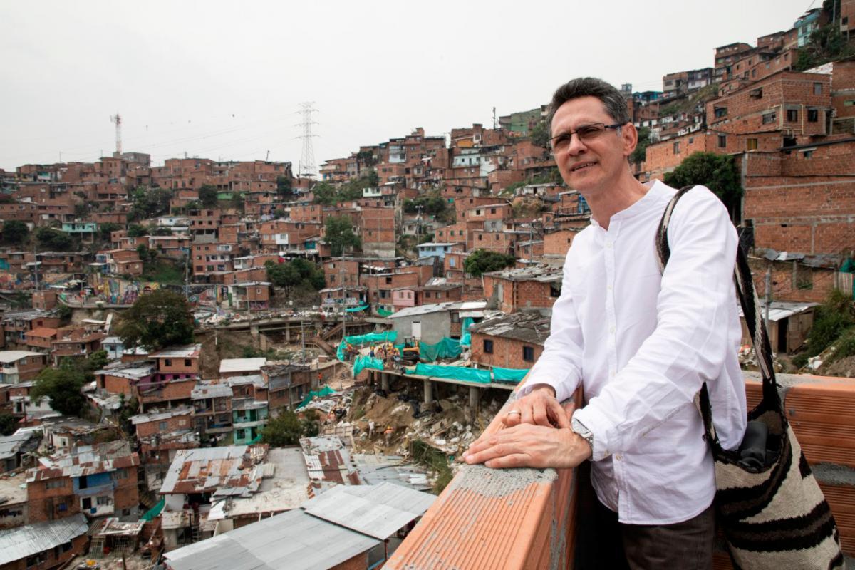 El escritor colombiano Pablo Montoya posa para una fotografía en la Comuna 13 de Medellín, al fondo, se ven las casas de la zona.