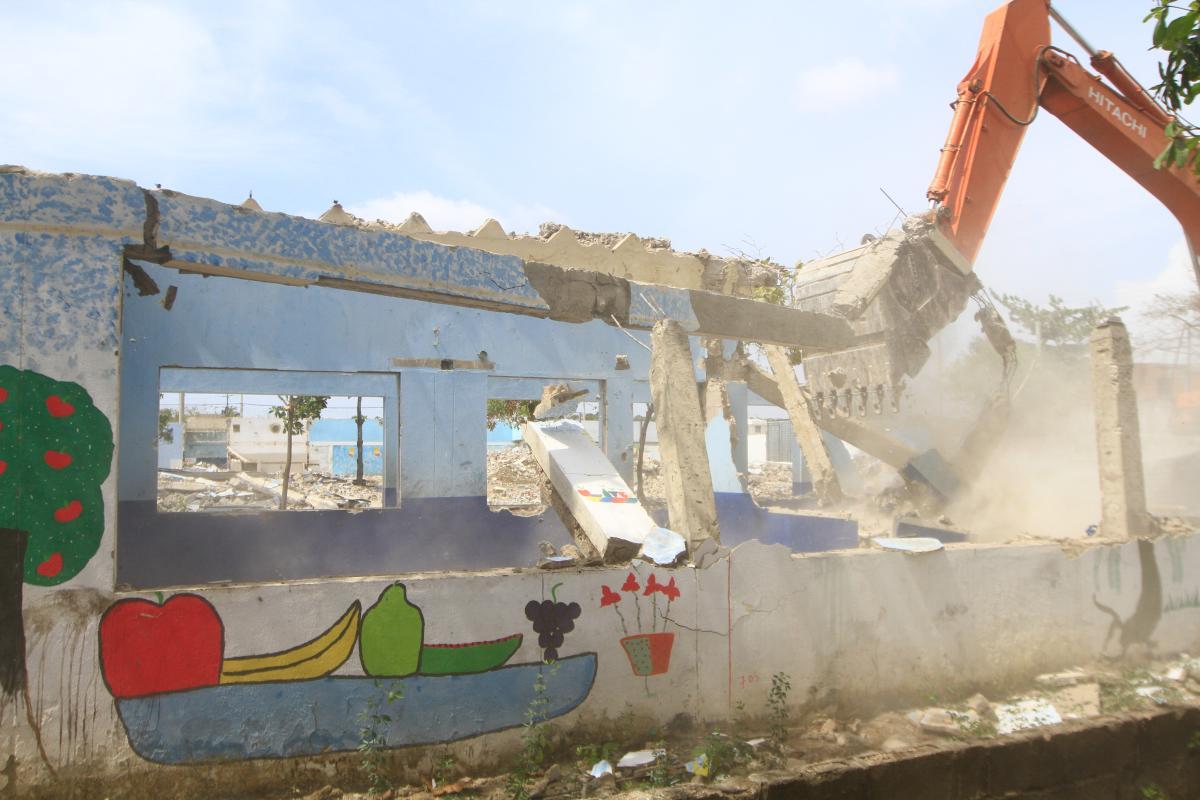 El brazo de una excavadora giratoria derriba una de las paredes de la Institución Educativa San Felipe Neri, en el barrio Olaya Herrera de Cartagena de Indias, Colombia. Se trata de una pared pintada con dibujos infantiles.