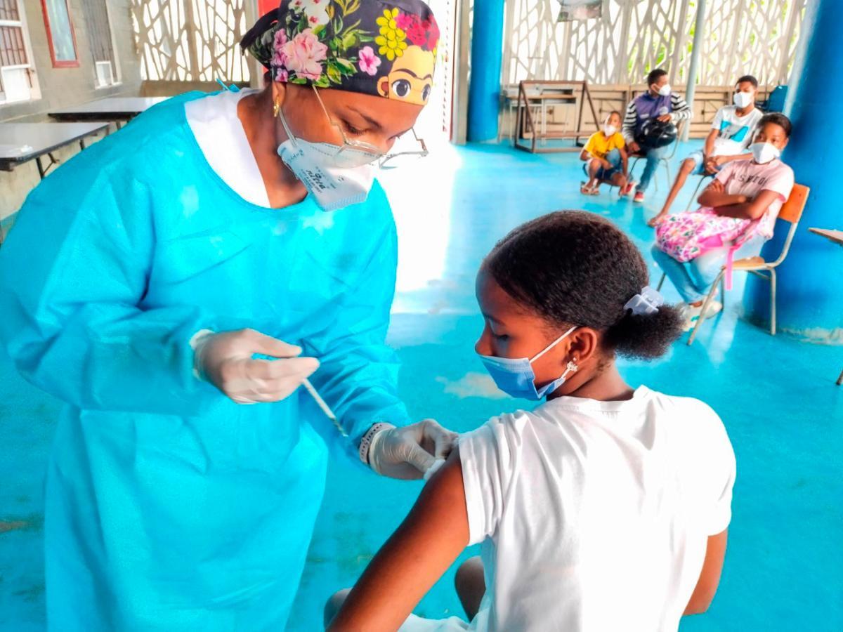 Personal médico administrando vacuna a estudiante contra la COVID 19