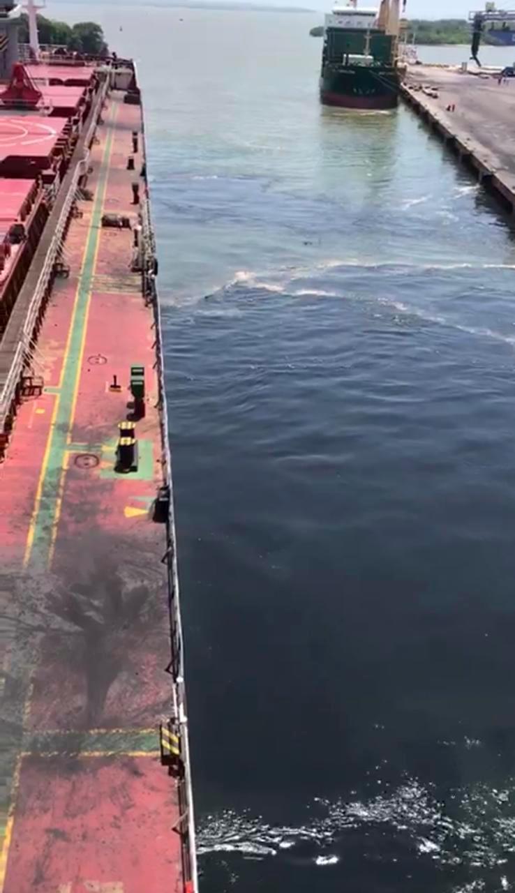 El vídeo muestra a dos operarios lavando con una manguera la placa de concreto del muelle, retirando los residuos de carbón, y en el agua una mancha negra. //Capturas del video