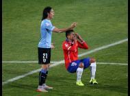 Gonzalo Jara cae tras recibir un manotazo de Edinson Cavani.