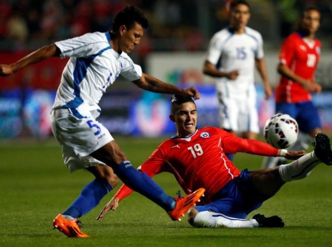 Jugadores de Chile y El Salvador disputan un balón durante el amistoso.
