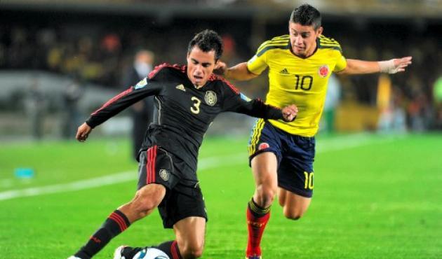AFP  EITAN ABRAMOVICH - Héctor Acosta, de México, disputa el balón con James Rod