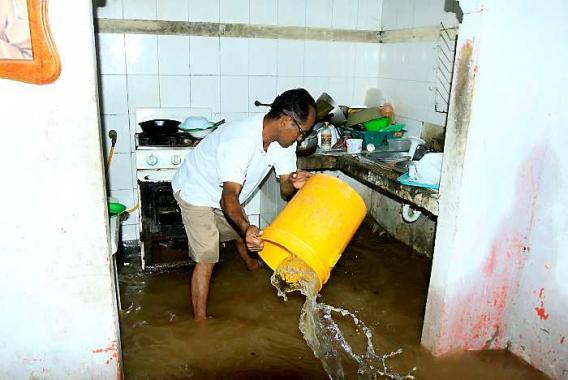 Los damnificados achican el agua que se metió a sus casas en la madrugada de aye