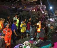 Un autobús accidentado yace tendido sobre un costado a un lado de la carretera mientras un grupo de personas observa los restos, el 21 de marzo de 2018 en la provincia de Nakhon Ratchasima, en Tailandia.