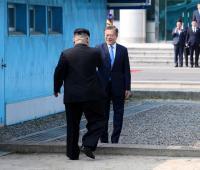 El presidente surcoreano Moon Jae-in (d) y el líder norcoreano Kim Jong-un (i) se dan la mano en la línea de demarcación militar (MDL), en una ceremonia de bienvenida en el lado sur de la frontera militarizada que separa a ambos países, antes de iniciar su histórica cumbre el 27 de abril de 2018, en la aldea de Panmunjom en Paju (Corea del Sur). Moon y Kim estrecharon manos y conversaron brevemente en la frontera intercoreana, y a continuación pasearon escoltados por una guardia de honor tradicional coreana