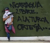 Un joven sostiene un lanza mortero junto a una pintada en repudio al gobierno del presidente Daniel Ortega hoy, 25 de abril de 2018, en Managua (Nicaragua).