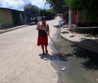 mujer barriendo en la calle