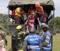 Niña bajando de camión con ayuda de militares