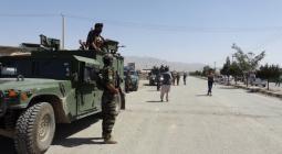 Oficiales de seguridad montan guardia en las carreteras que conducen al escenario de un ataque suicida en la provincia de Paktia