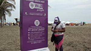 Mujer usando wifi gratis en la playa