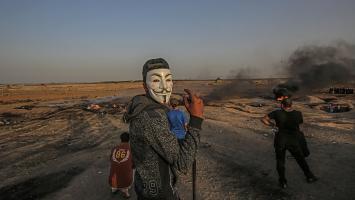 Un palestino protesta disfrazado con una máscara de Guy Fawkes durante las protestas cerca de la frontera entre Israel y Gaza, al este de Gaza City.