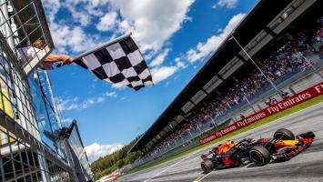 Max Verstappen de Red Bull cruza la meta como primero mientras ondean la bandera a cuadros en Viena. 2018.