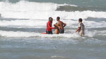 Salvavidas rescatando a un bañista en la playa