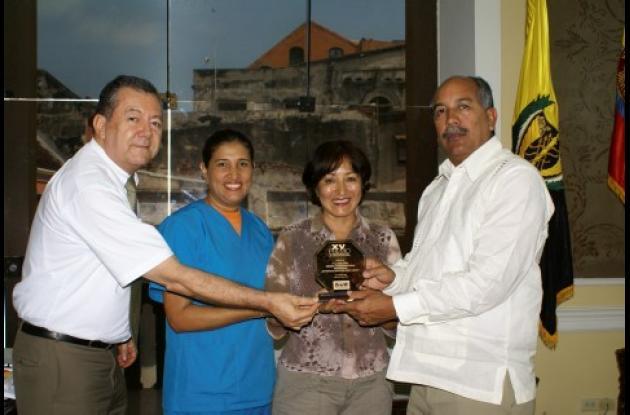 Los ganadores del premio: Miriam Pulido, (investigadora principal), quien sostiene la distinción, y los co-investigadores Marta Carmona y Antonio Díaz (ubicados a la izquierda), y el rector del a Universidad de Cartagena, Germán Sierra (a la derecha).