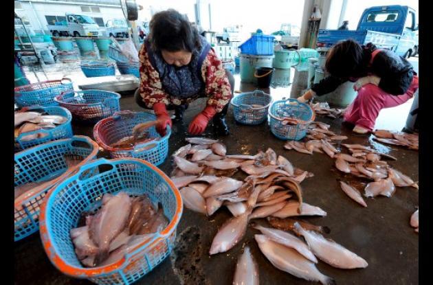 Mujeres japonesas con peces que tienen radiación acumulada