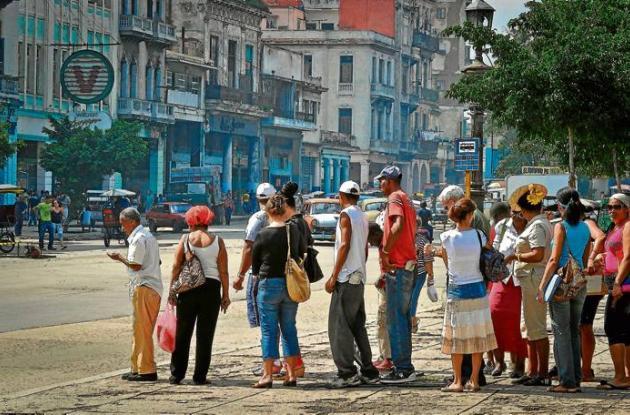 Los cubanos se alinean en una parada de autobús en La Habana.