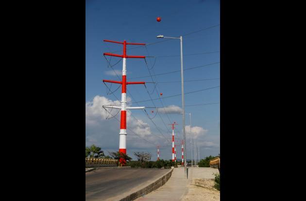 Los postes de alumbrado público que iluminan la vía Perimetral (derecha), serían afectados por la cercanía con la línea de 220 mil kilovoltios (izquierda) de Isa.