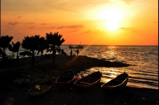 Las barcas, el mar lúbrico y susurrante, el sol como áurea esfera de amor, susurro de viento en las palmeras, festoneo de olas y de nubes, torbellinos de música y de luz: atardece en Tolú.