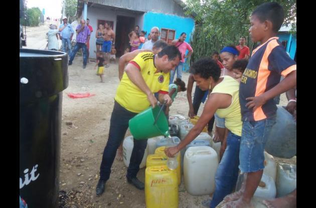 Las personas se abastecen de agua en los puntos asignados para ello.