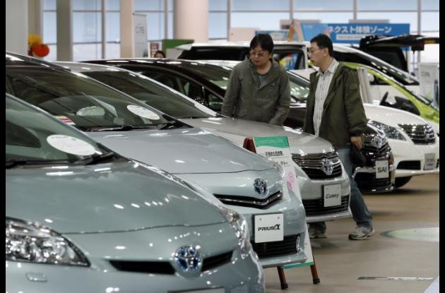 Dos hombres observando coches híbridos de Toyota en un concesionario en Tokio (Japón)