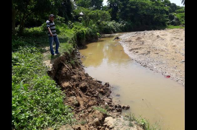 hombre muestra erosión a orillas del arroyo