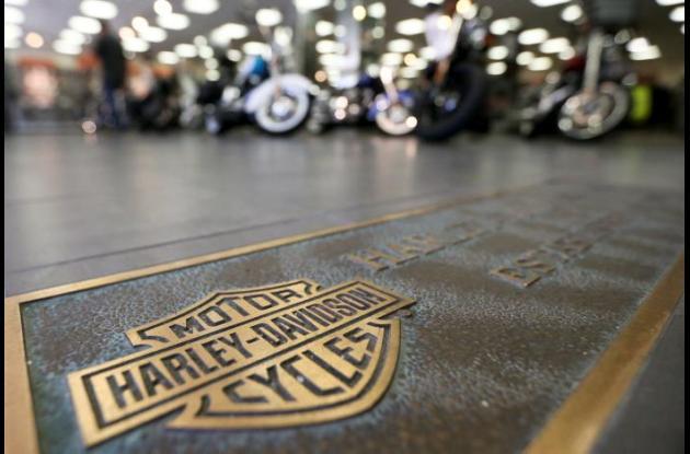 Foto de la marca Harley Davidson pintada en el piso de un almacén. Al fondo las motos