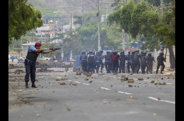 Miembros de las fuerzas antidisturbios de la Policía Nacional enfrentan a varios jóvenes