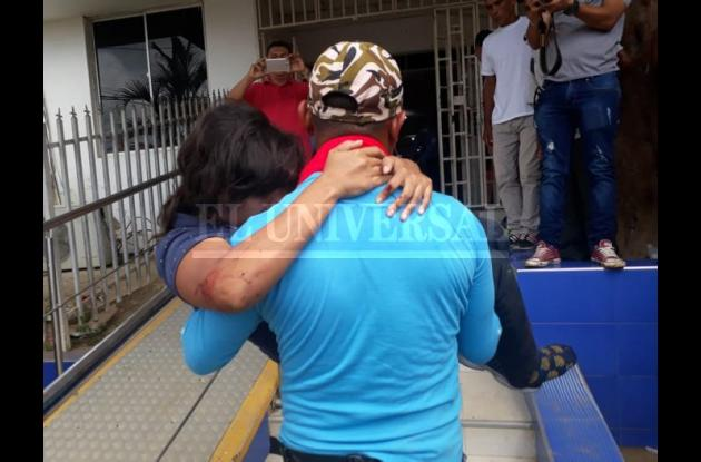 Un hombre carga a una mujer herida