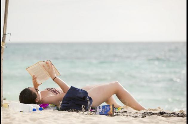 Mujer leyendo un libro en la playa
