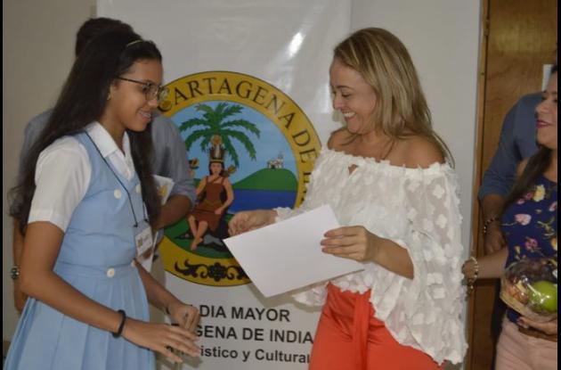 Estudiante ganadora recibiendo su premio de la secretaria de Educación