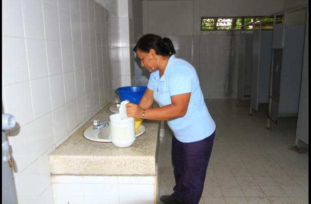 Operaria de aseo limpiando baños de institución educativa.