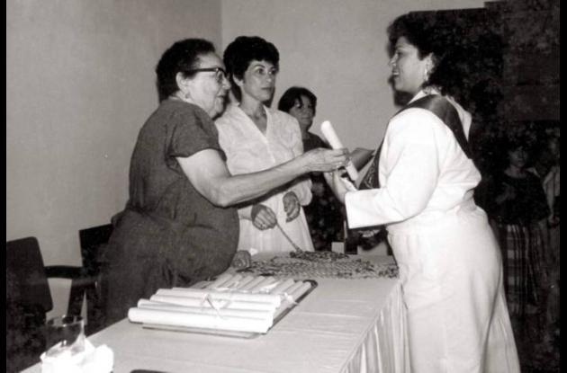 1985. Mercedes M. de Aldana y Ana Virginia Luna, entregando un diploma.