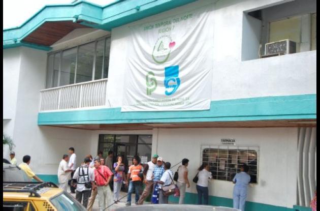 El periodista Mejía entró a la EPS y al ver la cola de unas 300 personas quiso hacer un informe sobre el tema, pero los directivos de la EPS dicen que no podía hacerlo y lo retuvieron en sus instalaciones.