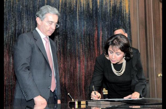 La nueva comisionada Ilse Bechara Castilla firmando la posesión ante el presidente Álvaro Uribe.