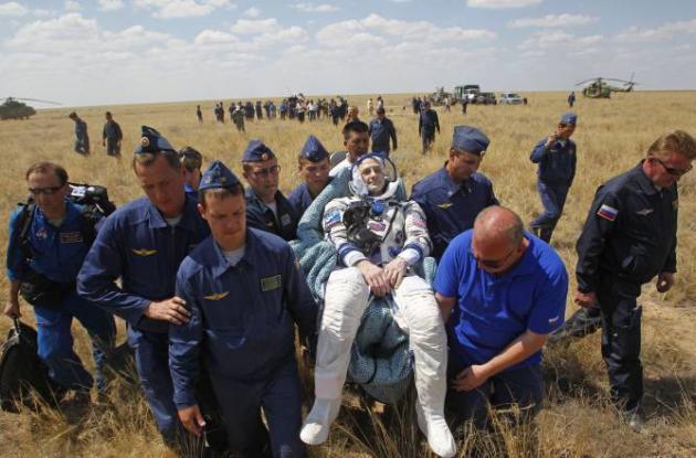 Miembros del equipo de rescate de la agencia espacial rusa llevan al astronauta