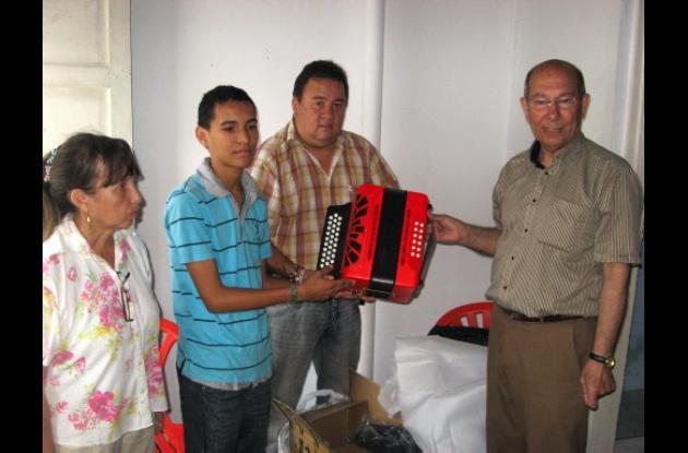 Antonio José Daza Orozco e Ismael Zuleta Guerra entregando el acordeón al menor.