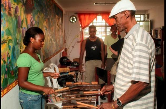 El maestro Gualajo (Gorro blanco) le enseña a una joven a interpretar la marimba