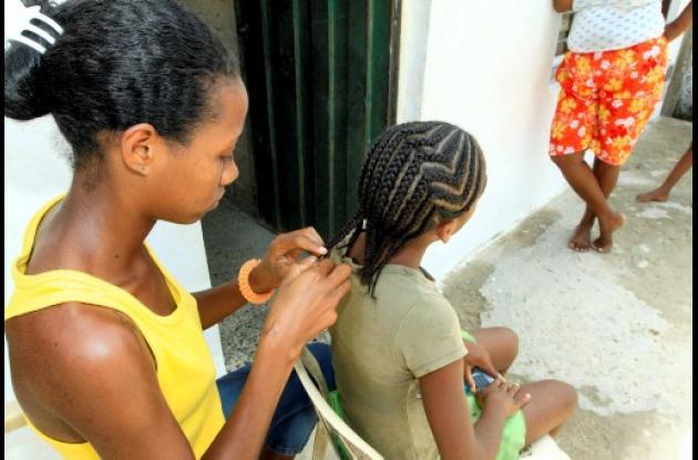 joven haciendo trenzas a una niña, en su casa