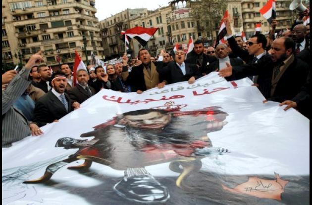 Abogados egipcios sostienen una imagen satírica de Hosni Mubarak.